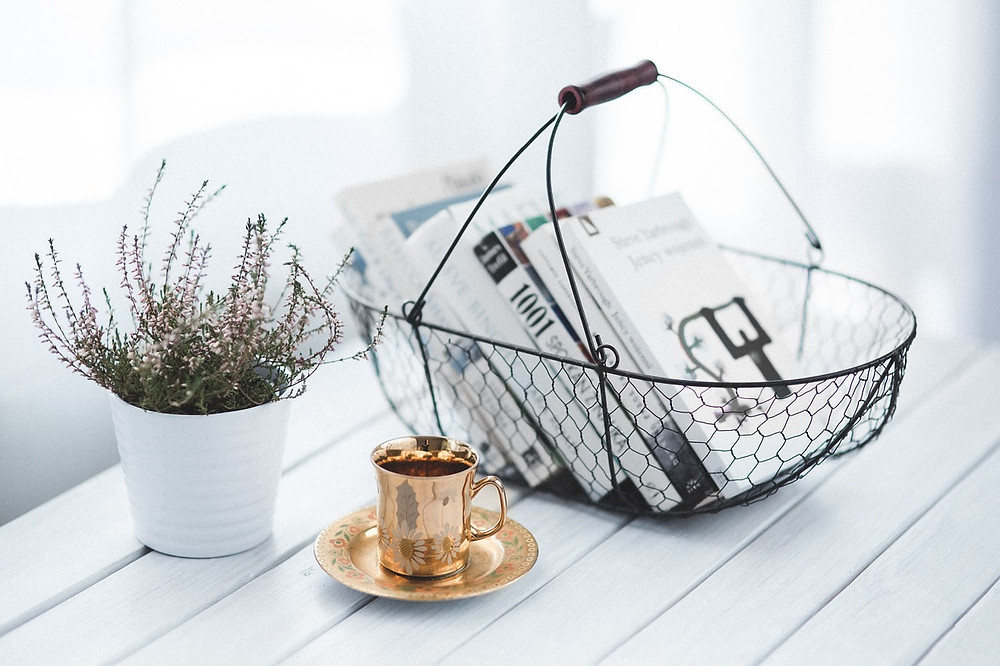 golden tea cup and basket of books in scandi background