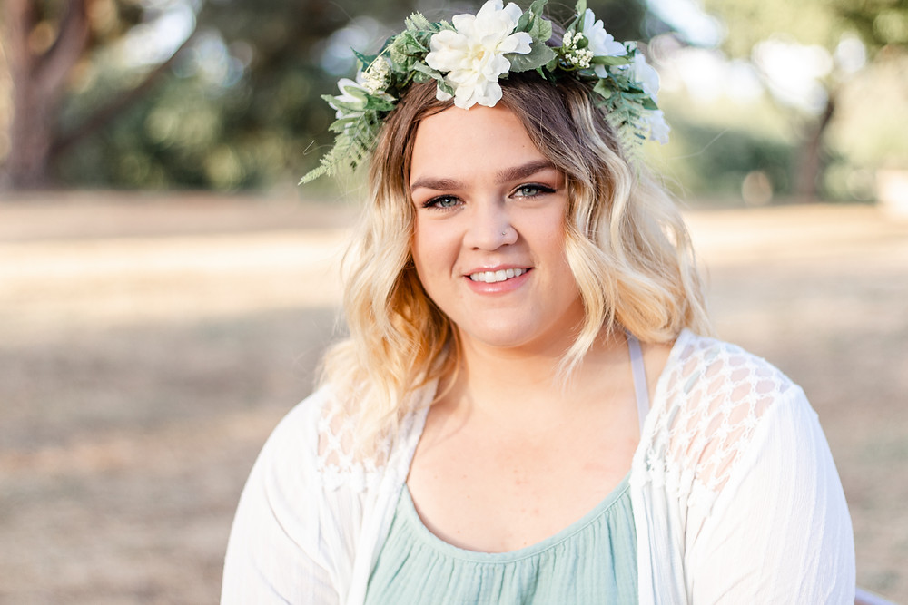 A recent graduate in Fresno, California smiles at the camera for a photography session. She is wearing a teal dress with a white lace sweater and a flower crown.