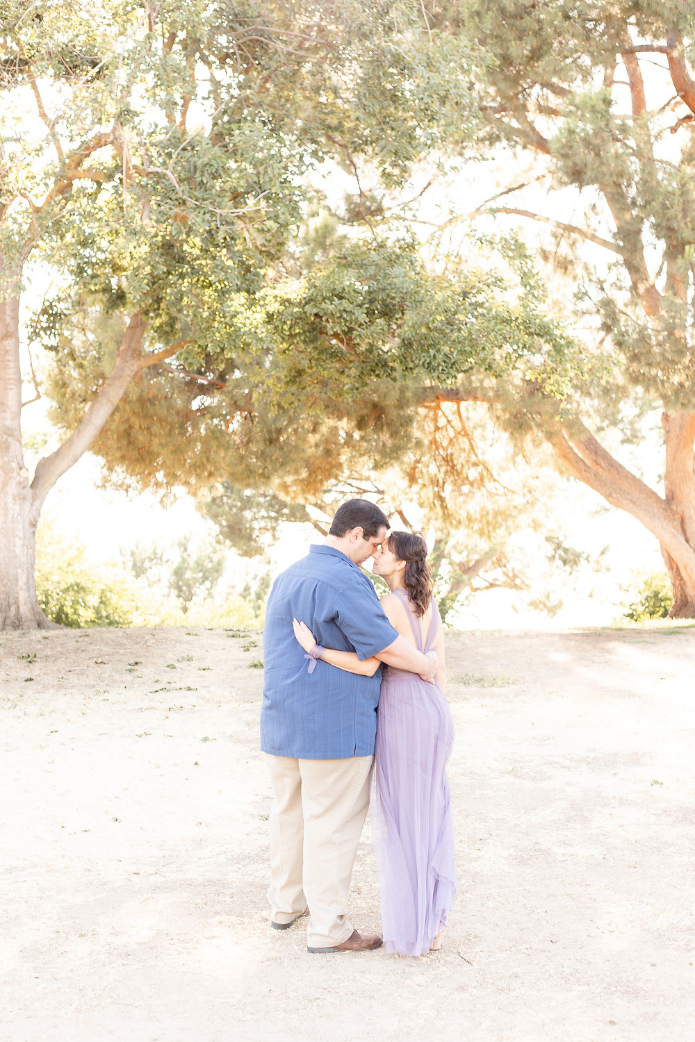 A couple in Woodward Park in Fresno, California hold each other closely with their backs facing the camera for a couples portrait session.