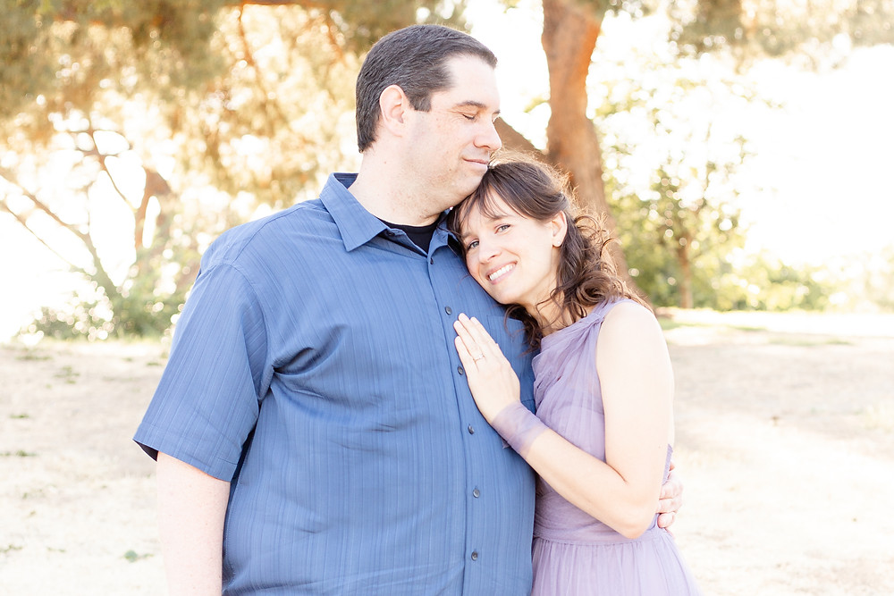 A couple in scenic Woodward Park in Fresno, California cuddles close for a couples photography session. The woman's hand is on the man's chest as he closes his eyes and she gazes at the camera.