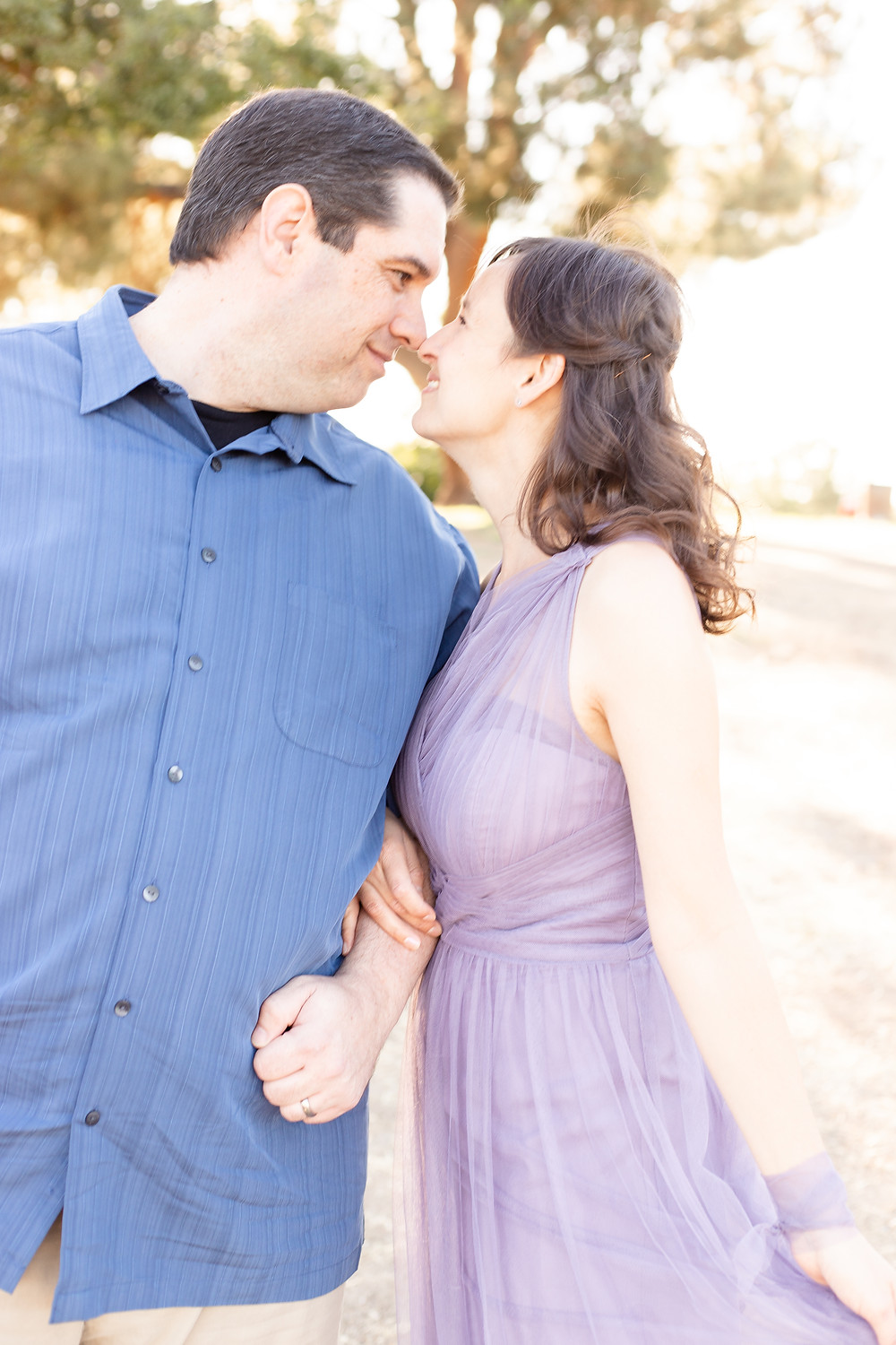 A man and woman in Woodward Park in Fresno, California lean towards each other and touch noses for a couples lifestyle portrait session..