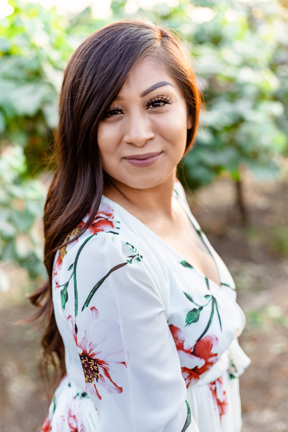 A young women does a portrait session with Ashley Norton Photography in a vineyard in Madera, California..