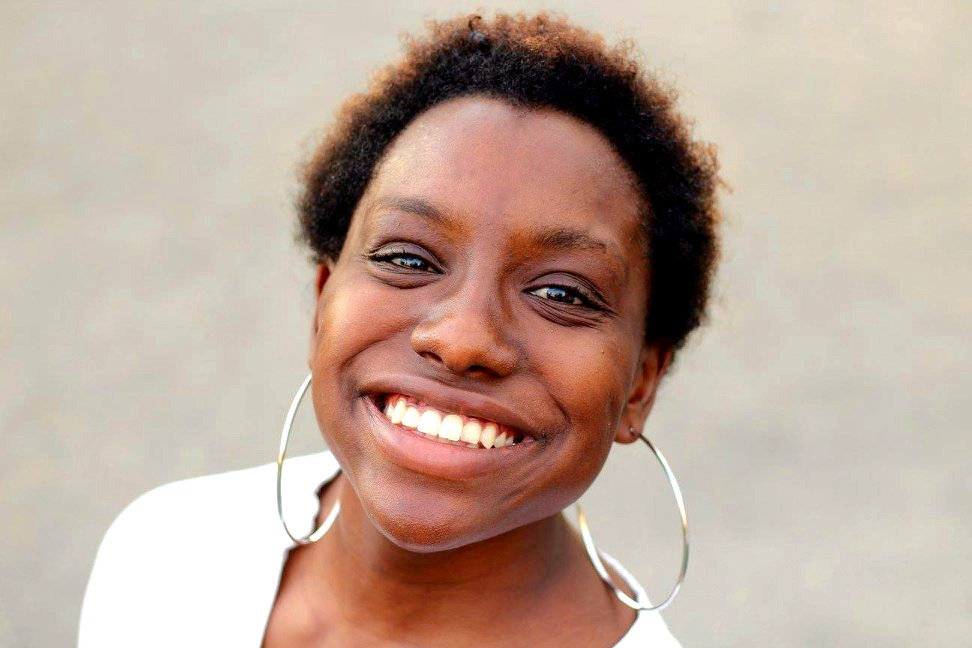 A young Black woman smiles up at the camera. Her hair is short and natural, and she is wearing silver hoop earrings with a white shirt.