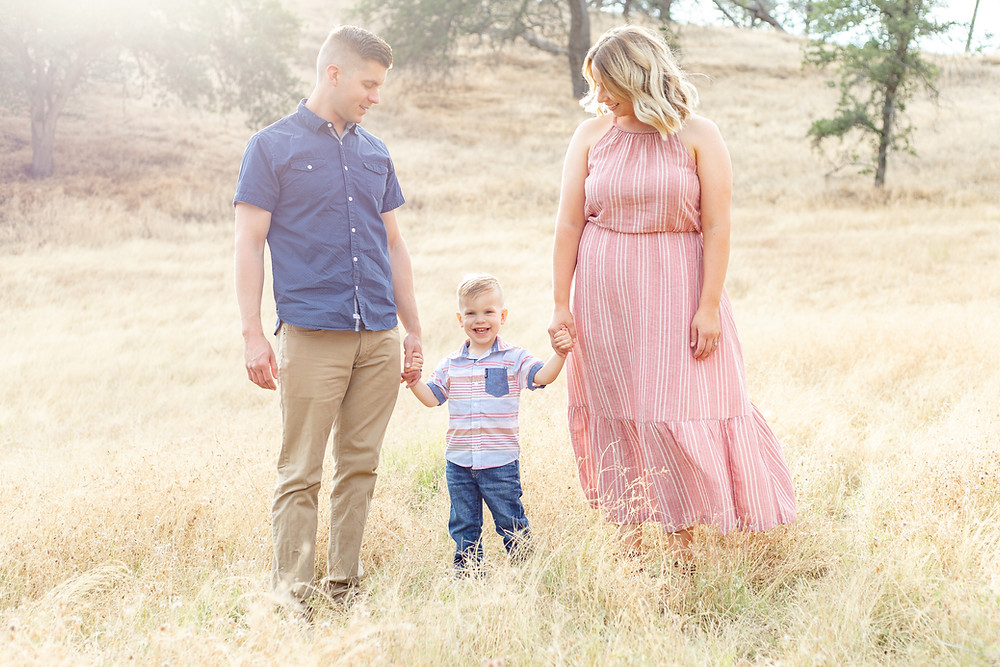 A young family stands in the middle of a golden field at Millerton Lake, California for family portraits. They hold their son's hand. Mom is wearing a long, blue and white stripped sleeveless maxi dress. Dad is wearing a dark blue shirt and tan pants. The young boy is wearing a striped blue and pink polo shirt with jeans.