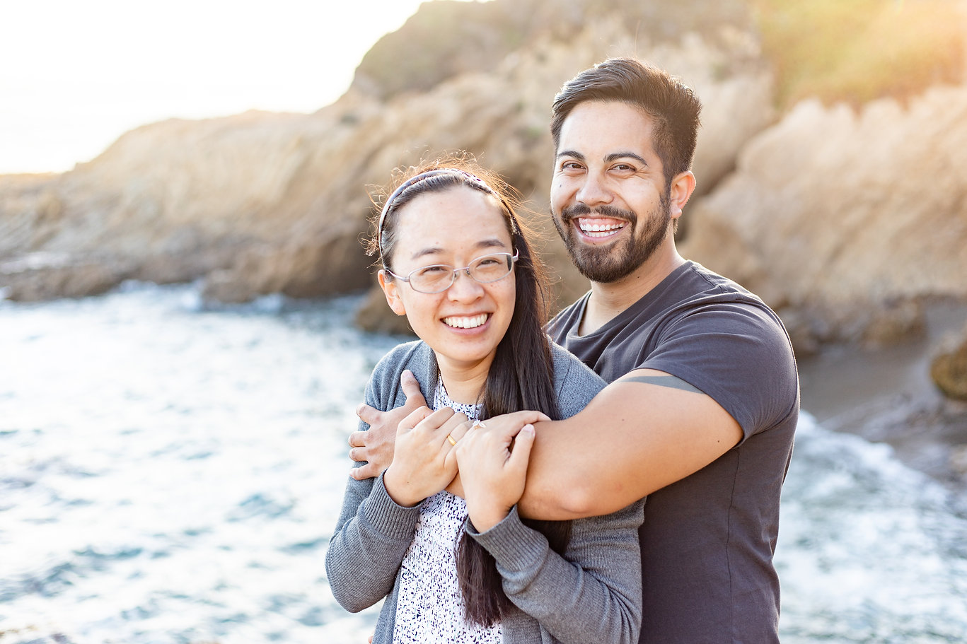 A couple stands together on a beach cliffside in California. They are newly engaged, smiling, as he holds his left arm across her chest. Her back is to him as she holds onto his forearm, where you can see her engagement ring.