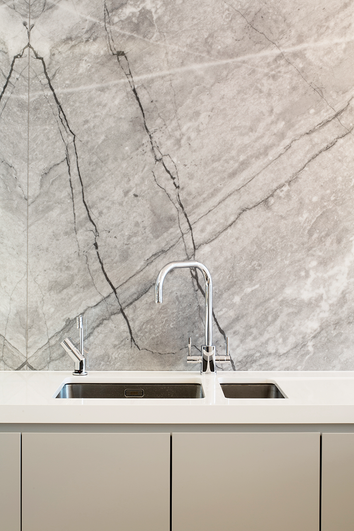Contemporary matt lacquered cabinetry with a white quartz worktop, painted glass splashback and a marble feature wall