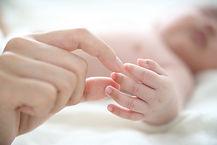 Madre che tiene il dito del bambino