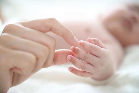 Mère tenant un doigt de bébé