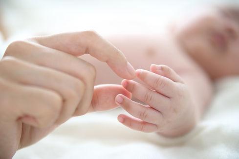 Madre sosteniendo bebé dedo