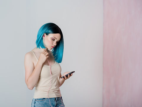 Young beautiful girl with blue hair is holding a smartphone, with are pink headphones in h