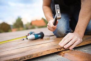 Handyman installing wooden flooring in p