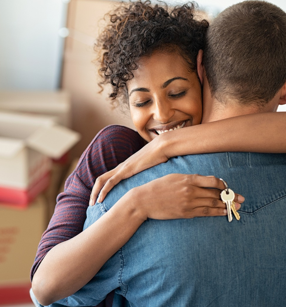 Happy couple hugs while wife holds keys after finding connection during coronavirus and shelter-in-place order in Chicago, IL. Online couples counseling, Illinois can help you feel better today.