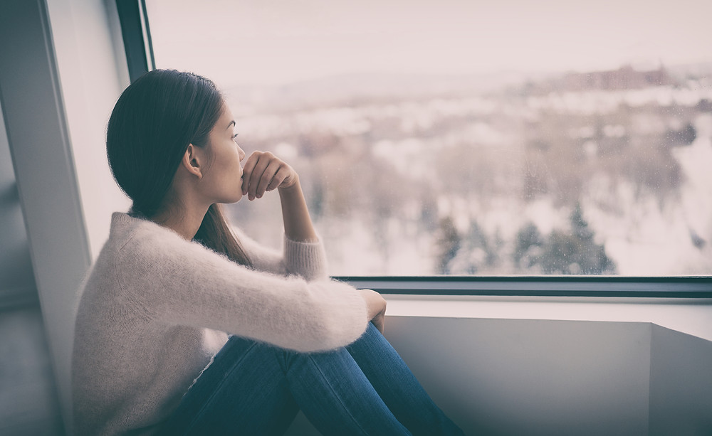 Woman looking out the window, sitting with her hand on her face in concern about Coronavirus and stress about the global pandemic. Online therapy in Illinois will help with anxiety and depression.