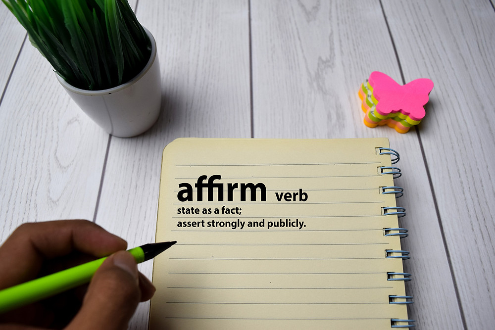 "hand holding a pencil with a notebook with the words ""affirm. verb. state as a fact; assert strongly and publicly."" written. Anxiety Treatment can be effective with online counseling, telehealth or Online Therapy in Illinois"