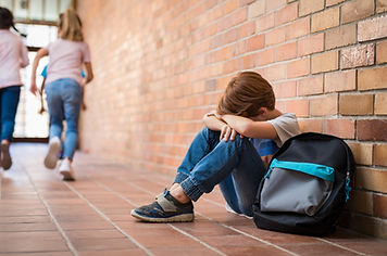 Sad Boy Sitting Alone on the floor against a brick wall at school. Therapy for Sexual abuse in Madison, WI is here with PTSD treatment and Trauma treament in Madison, WI. You can also get help with online therapy in Wisconsin for children, teens and adults.