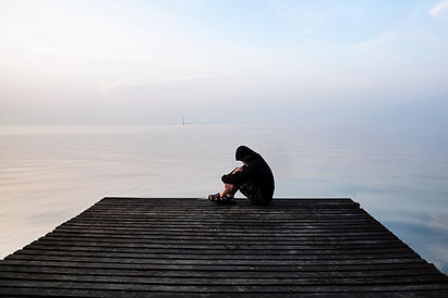 Person sitting at the end of a dock, looking upset and depressed. You can get depression therapy in Madison, WI 53703 at Golden Vibes Counseling for depression treatment with online therapy in Wisconsin