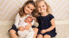 Big sisters adore their new baby brother!
