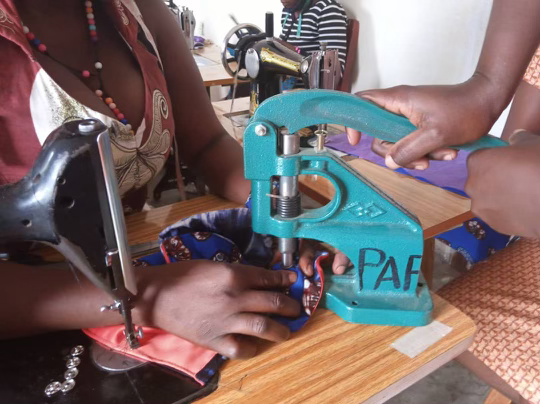 One woman is holding a piece of fabric while the other is punching a hole into the fabric.