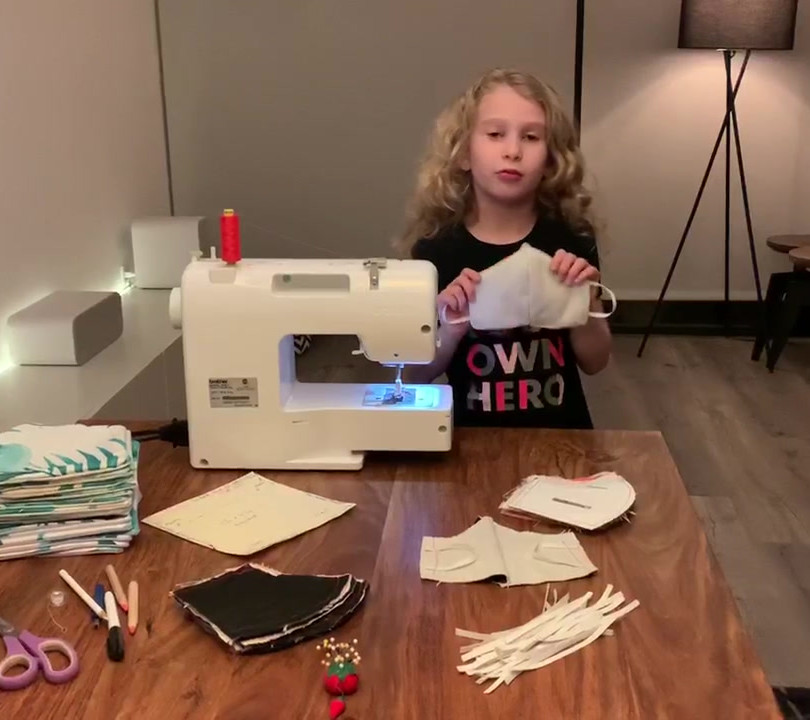 A young little blond girl is standing behind her sewing machine explaining her work for Design Lab