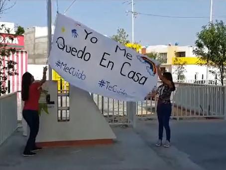 """Maestros izan bandera blanca con la frase """"Yo me quedo en Casa"""" en el patio de su escuela"""
