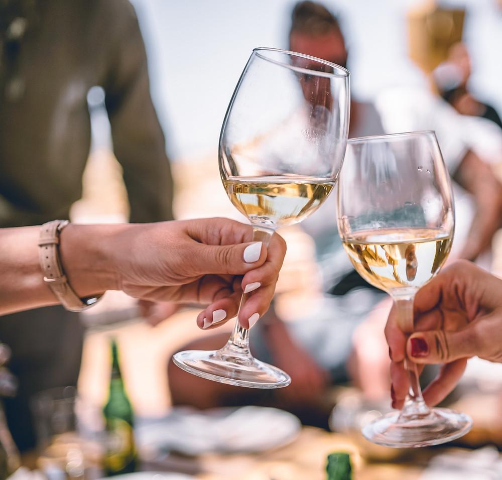 white wine in glasses toasting