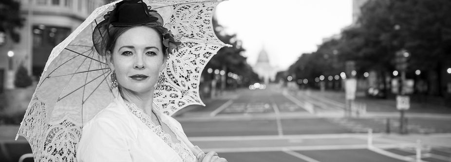 A black and white photo of Off the Mall Walking Tours founder, Katie Kirkpatrick standing in front of the U.S. Capitol Building