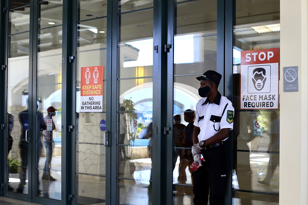 A security guard stands at the entrance of to uphold COVID-19 Protocols.