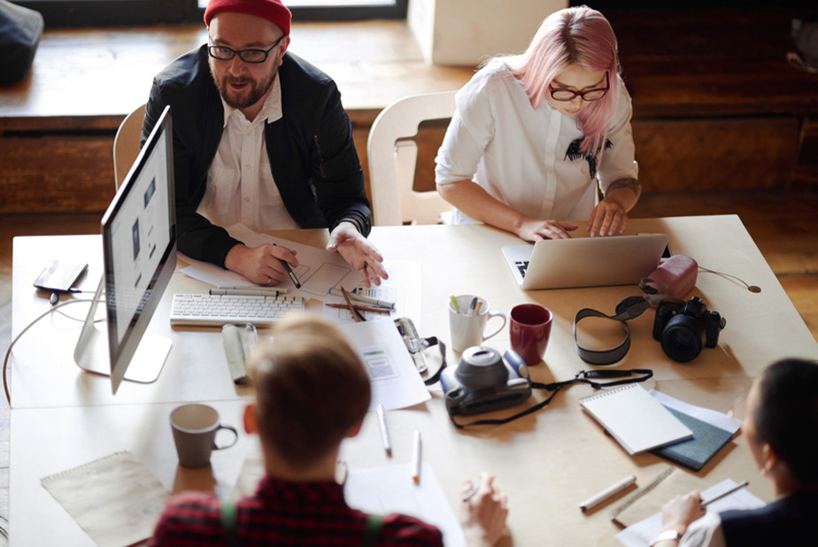 Men and women working around a table with computers, paper, and pencils.