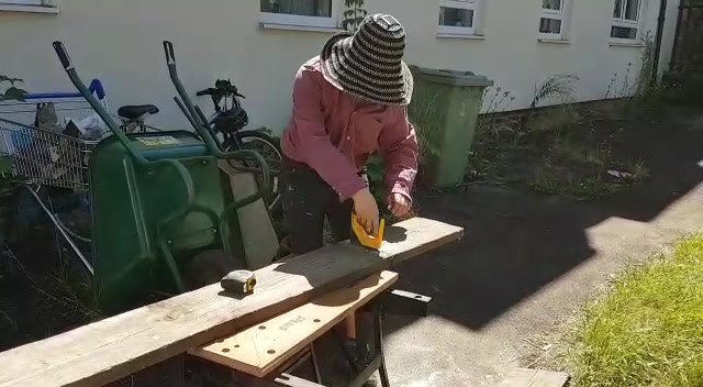 Hand sawing reclaimed scaffold boards