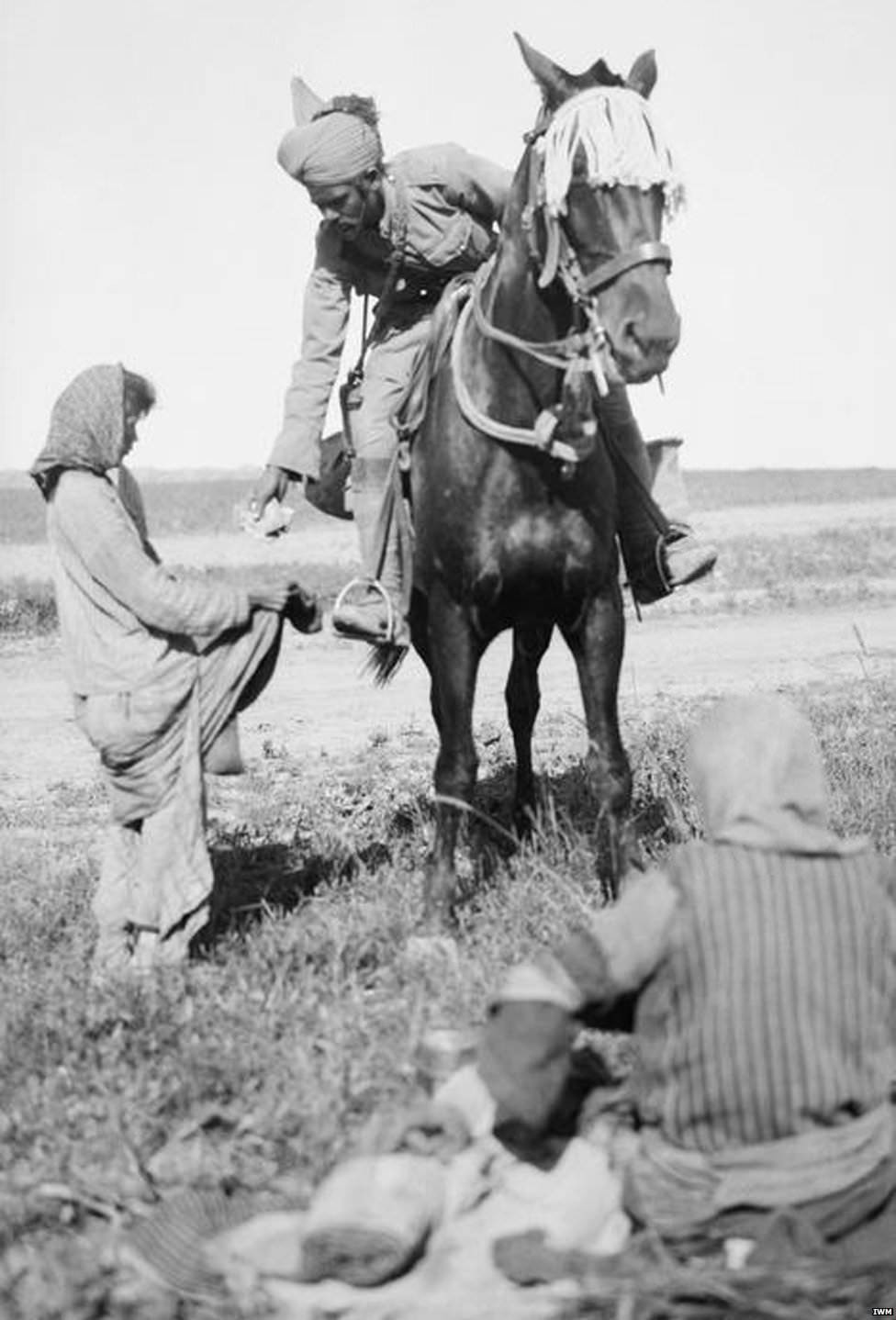 A Sikh Indian cavalryman who has found two starving Christian girls in the desert in Armenia. He leans down from his horse to give one of them half his rations. At the time the men themselves were on short rations, during World War I (Armenian genocide by the Ottoman empire.)