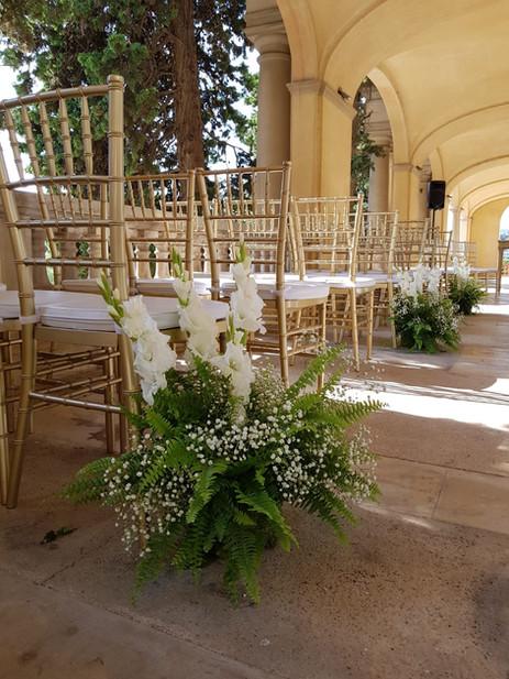 Ceremonia con camino de plantas y flores blancas
