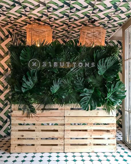 Photocall corporativo tropical con pallets y verdes naturales