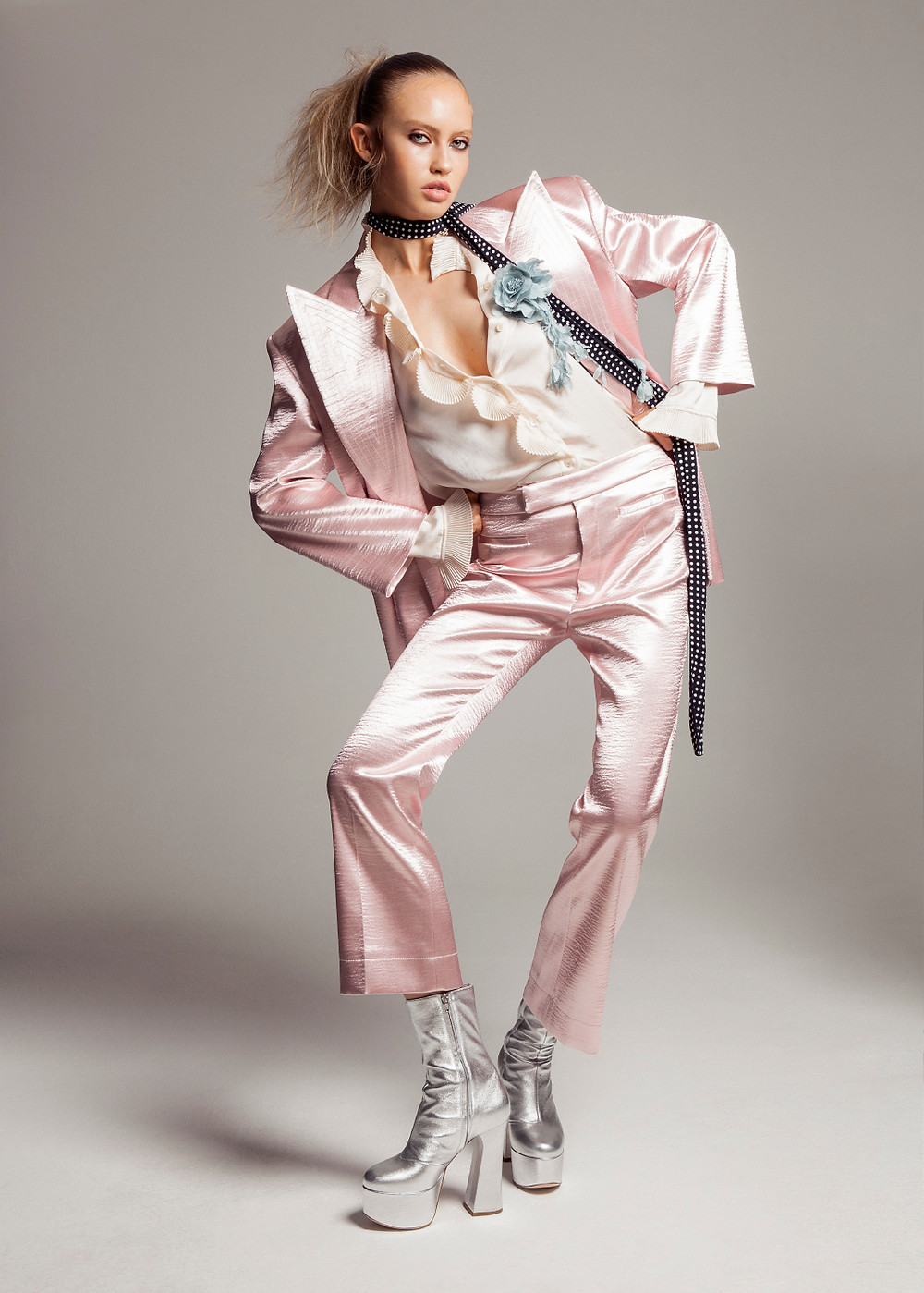 Oversized satin blazer with matching 70's cropped trousers, matte satin shirt with ruffles, polka dot crepe scarf, satin floral broach and metallic leather platform ankle boots, all by Philosophy di Lorenzo Serafini