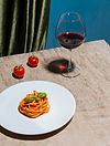 Pasta dish and a glass of red wine