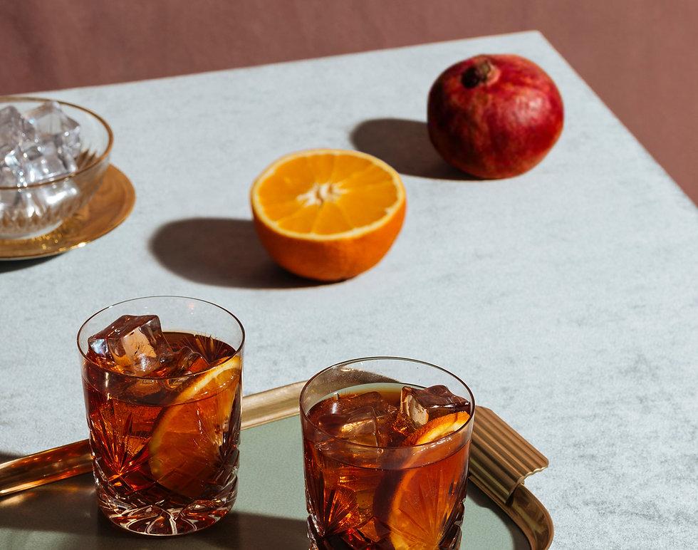 Cocktails, pomegranate and half an orange