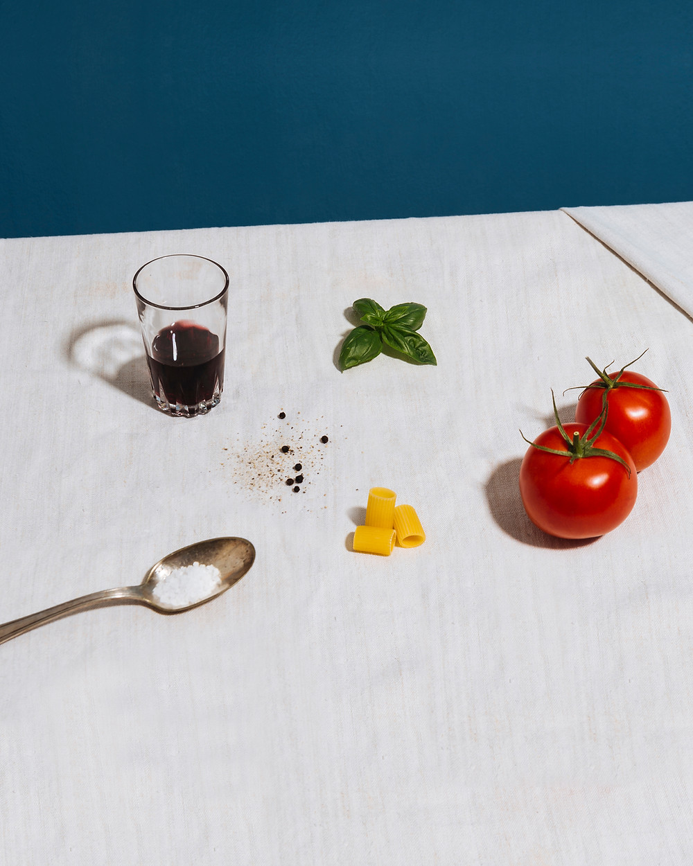 Glass of wine, basil leaves, tomatoes, dry pasta and some salt grains on a white tablecloth