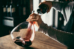 Hand holding decanter while pouring red wine