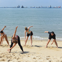 Stretching before their beach boxing session