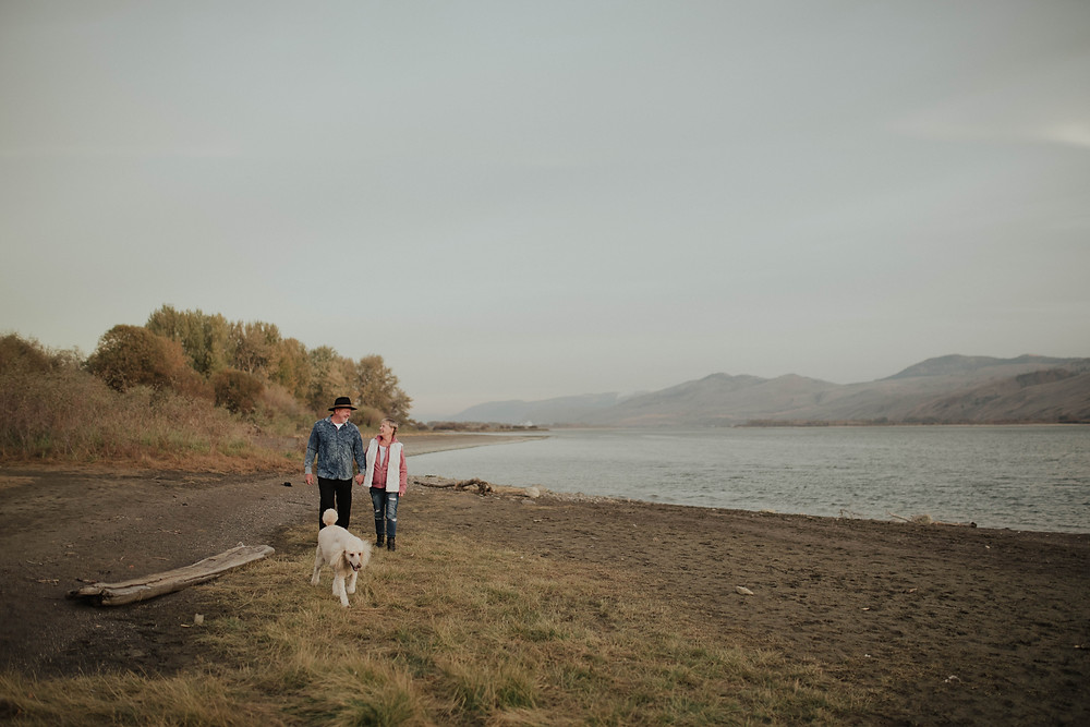 Salmon Arm photographer couple walking on the beach with their dog at tranquil farm