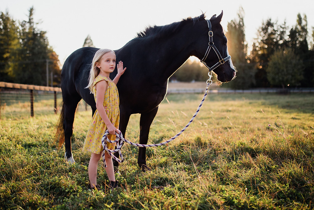 Blond girl in a golden dress with her chestnut horse