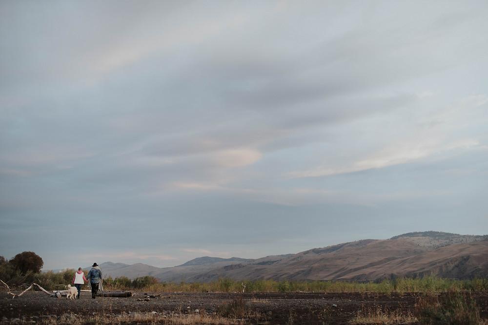 Salmon Arm photographer couple walking on the beach at tranquil farm