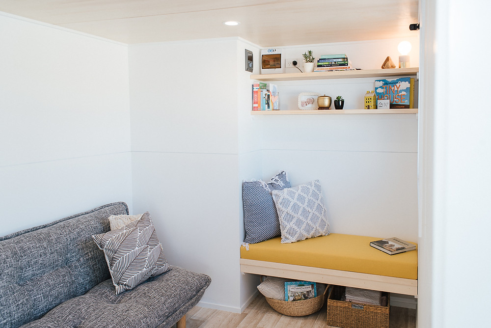 Tiny house lounge room with bench seating and shelving.