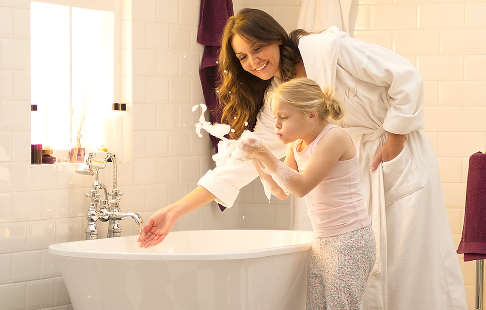 little girl and mum filling the bath and blowing bubbles.