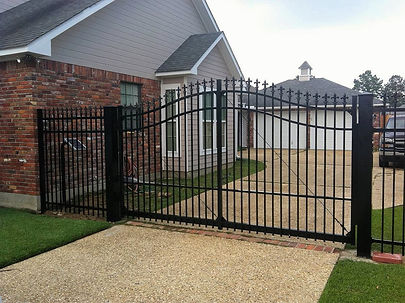A black electric gate outside a house