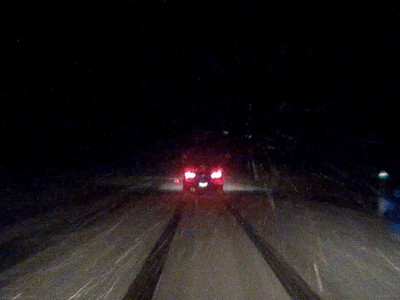 Dash cam screen grab during a brief let-up in the snowfall, crawling onward somewhere in the dark on Highway 7.