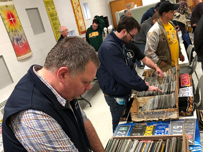 Dave Grant looks for 1973 plates in the foreground, while busy trading happens in the background.