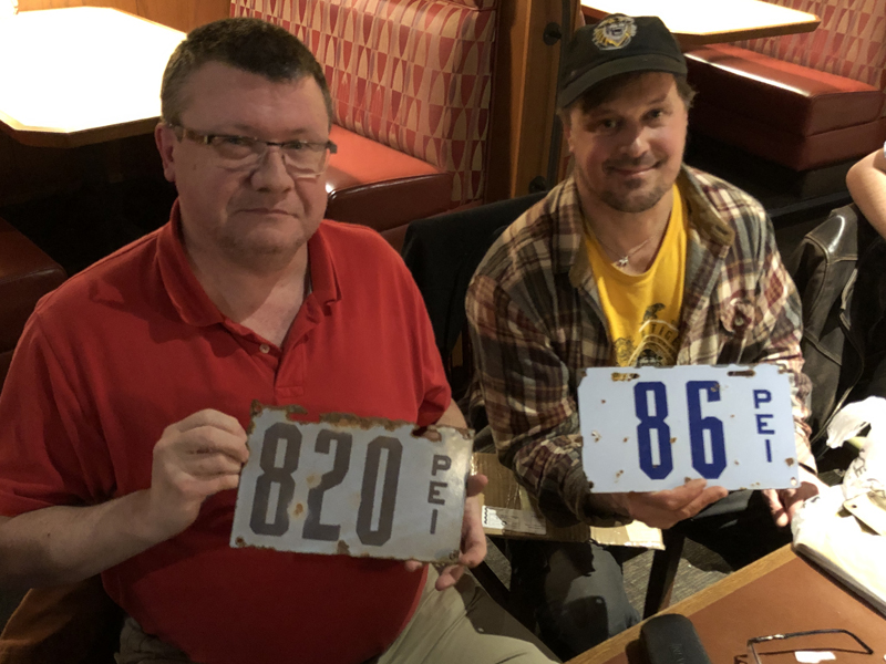 Mike holds a real 1919 PEI porcelain plate. Joe holds a reproduction with fake rust spots.
