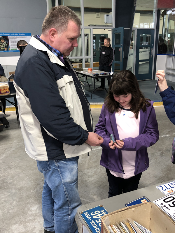 Dave Grant helps his daughter Leah choose a motorcycle plate.
