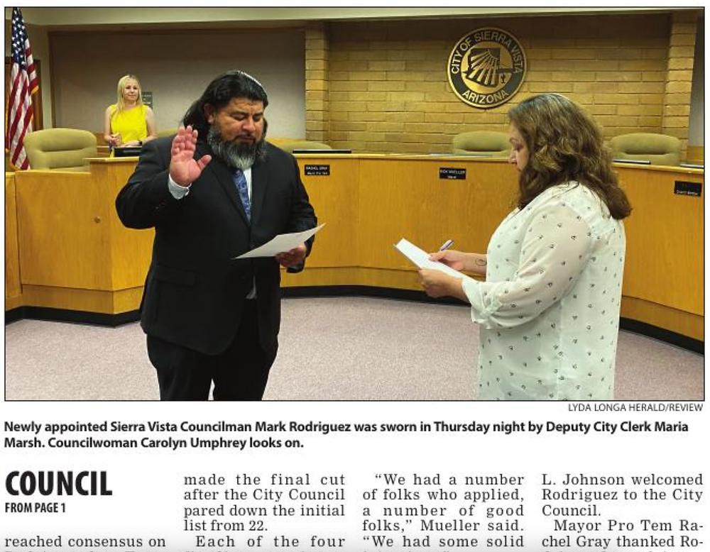 newspaper picture of councilmember being sworn in