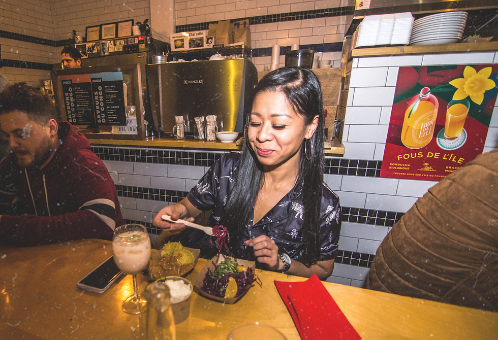 Asian girl eating bissap hibiscus salad and Amarula cocktail and peanut chicken mwamba at Mokili African restaurant pop-up event